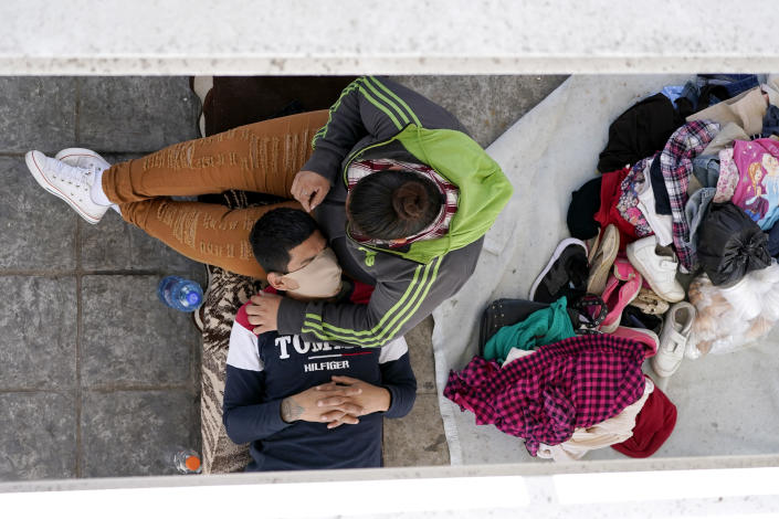 """Migrants who were caught trying to cross into the U.S. and were deported rest under a ramp that leads to the McAllen-Hidalgo International Bridge on Thursday, March 18, 2021, in Reynosa, Mexico. The fate of thousands of migrant families who have recently arrived at the Mexico border is being decided by a mysterious new system under President Joe Biden. U.S. authorities are releasing migrants with """"acute vulnerabilities"""" and allowing them to pursue asylum. But it's not clear why some are considered vulnerable and not others. (AP Photo/Julio Cortez)"""