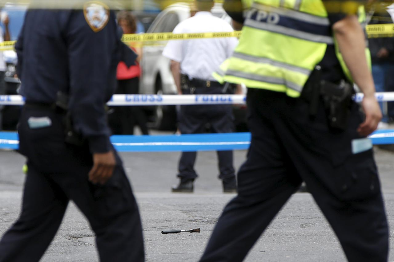 REFILE - ADDITIONAL CAPTION INFORMATION   A hammer lies on the ground at a crime scene as members of the NYPD police stand by at the intersection of 37th street and 8th avenue in midtown Manhattan in New York, May 13, 2015.  A hammer-wielding man who hit three people on the head in tourist-packed areas of New York City earlier this week has been shot in a confrontation with police, New York media reported on Wednesday.   REUTERS/Shannon Stapleton