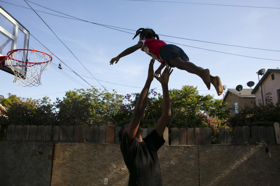 James Posey III, 14, tosses a neighbor's kid in the air while playing with her in the Watts neighborhood of Los Angeles, Monday, June 15, 2020. Watts has long been associated with deadly and destructive rioting in 1965. This summer when widespread mostly peaceful protests for racial justice across the U.S. have been accompanied at times by vandalism and other crimes, Watts has been peaceful. One lawmaker says the residents learned long ago that it didn't pay to burn their own neighborhood. (AP Photo/Jae C. Hong)