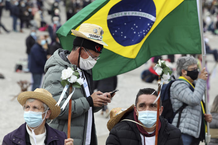A pilgrim wearing a face mask checks his phone while another holds a Brazilian flag while waiting for the start of the religious ceremonies at the Catholic shrine in Fatima, Portugal, Thursday, May 13, 2021. In view of the coronavirus pandemic, the shrine has limited to 7,500 the number of pilgrims that can be present during this year's May 12 and 13 celebrations usually attended by hundreds of thousands. (AP Photo/Ana Brigida)