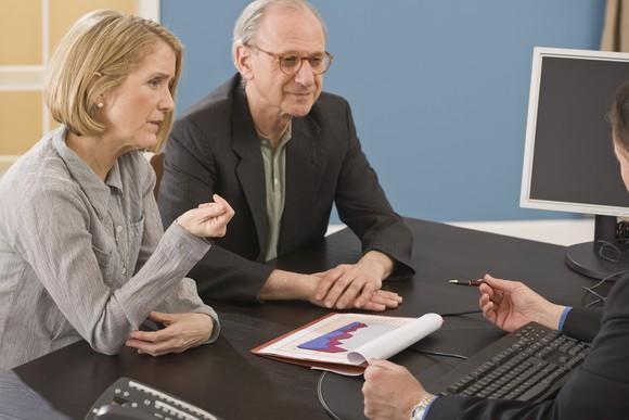 Senior couple at a desk, reviewing a chart with a person across from them.