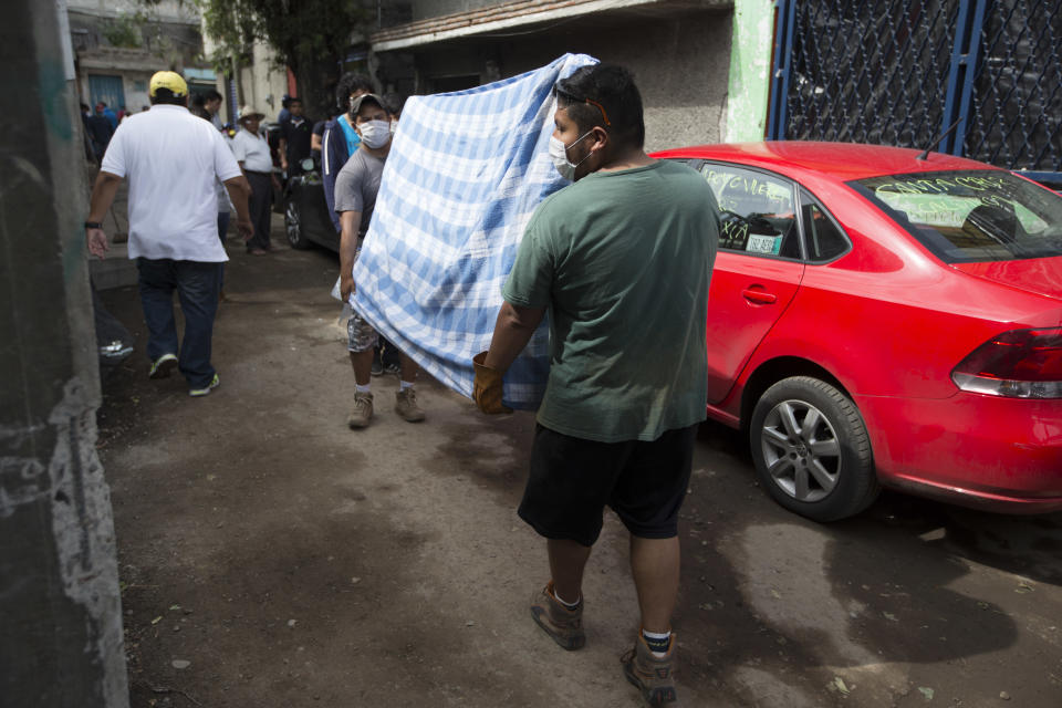 <p>Neighbors carry a bed, salvaged from a damage home in San Gregorio Atlapulco, Mexico, Friday, Sept. 22, 2017. Mexican officials are promising to keep up the search for survivors as rescue operations stretch into a fourth day following Tuesday's major earthquake that devastated Mexico City and nearby states. (AP Photo/Moises Castillo) </p>