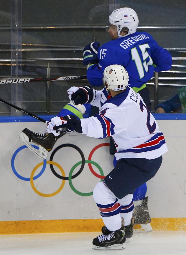 Slovenia's Blaz Gregorc (15) is checked into the boards by Team USA's Ryan Callahan (24) during the first period of their men's preliminary round ice hockey game at the 2014 Sochi Winter Olympics, February 16, 2014. REUTERS/Brian Snyder (RUSSIA - Tags: OLYMPICS SPORT ICE HOCKEY)