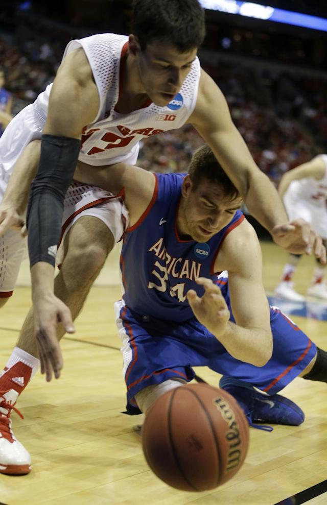 Wisconsin forward Duje Dukan (13) and American center Tony Wroblicky (34) battle for a loose ball during the second half of a second-round game in the NCAA college basketball tournament Thursday, March 20, 2014, in Milwaukee. (AP Photo/Morry Gash)