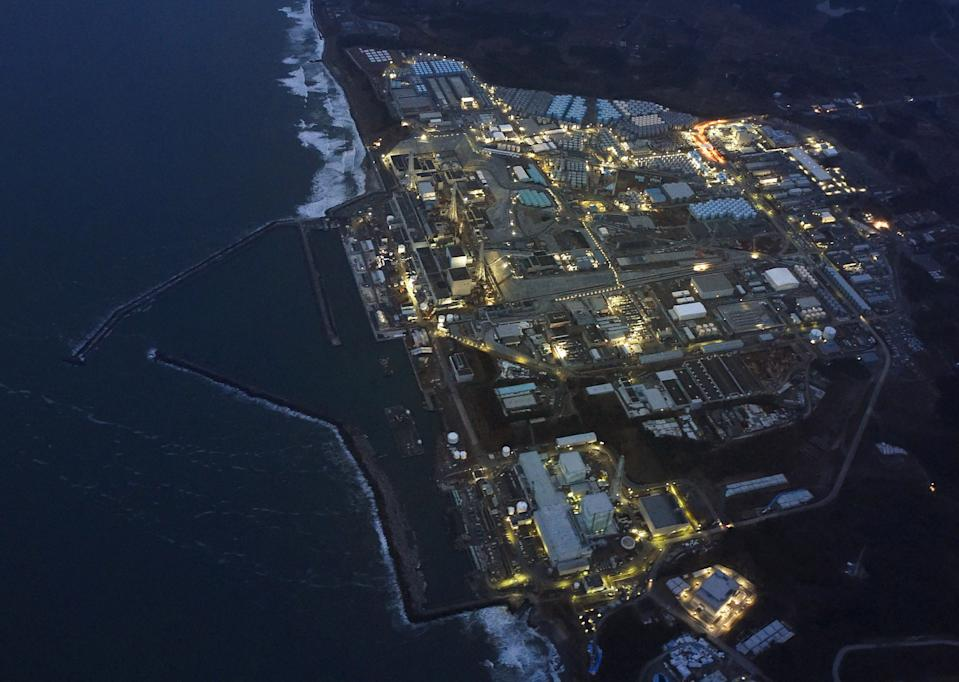 <p>Tokyo Electric Power Co.'s (TEPCO) tsunami-crippled Fukushima Daiichi nuclear power plant is illuminated for decommissioning operation in the dusk in Okuma town, Fukushima prefecture, Japan, in this aerial view photo taken by Kyodo March 10, 2016, a day before the five-year anniversary of the March 11, 2011 earthquake and tsunami disaster. REUTERS/Kyodo</p>