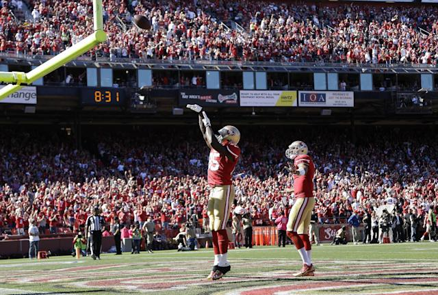San Francisco 49ers tight end Vernon Davis (85) shoots the ball over the goal post after scoring on a 61-yard touchdown reception from quarterback Colin Kaepernick, right, during the second quarter of an NFL football game against the Arizona Cardinals in San Francisco, Sunday, Oct. 13, 2013. (AP Photo/Ben Margot)