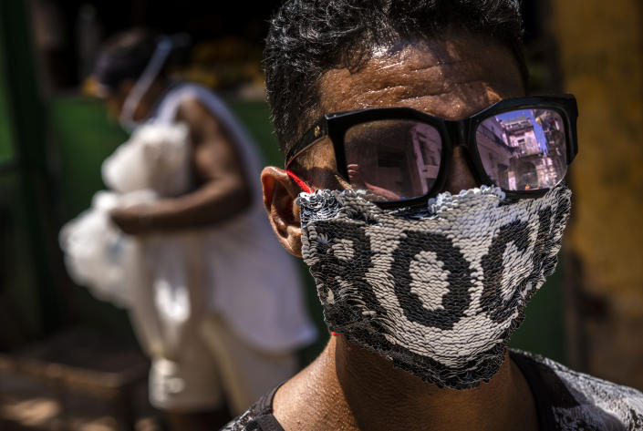 A youth wears a homemade face mask made of sequenced fabric amid the spread of the new coronavirus in Old Havana, Cuba, Friday, March 27, 2020. (AP Photo/Ramon Espinosa )