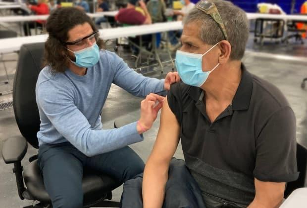 Mario Alonso Mejia Garcia, 56, receives his first COVID-19 vaccine in Edmonton in April. The province passed a major milestone this week, having vaccinated more than 2 million Albertans. (AHS - image credit)