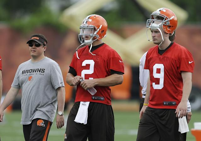 Cleveland Browns quarterback Johnny Manziel (2) walks off the field with quarterbacks coach Dowell Loggains, left, and quarterback Connor Shaw (9) after a mandatory minicamp practice at the NFL football team's facility in Berea, Ohio Tuesday, June 10, 2014. (AP Photo/Mark Duncan)