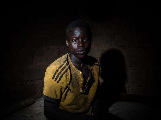Karim Bakary, 16, from Burkina Faso, photographed inside a hut out in the woods near the cocoa farm where he works and sometimes takes shelter in with other children