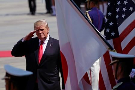 U.S. President Donald J. Trump salutes to national flags of the United States and Japan as he reviews the guard of honor during a welcoming ceremony at the Imperial Palace in Tokyo