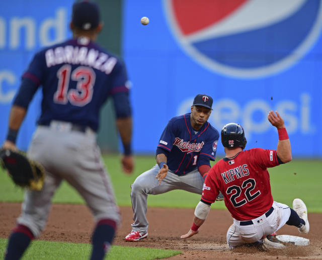 Cleveland Indians' Jason Kipnis (22) slides as Minnesota Twins' Jorge Polanco, center, attempts to field the throw from Ehire Adrianza (13) in the fourth inning of a baseball game, Friday, July 12, 2019, in Cleveland. Jose Ramirez would be safe at first base. (AP Photo/David Dermer)