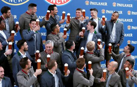 Bayern Munich's soccer team wearing traditional attire, toasts with beer during photocall in Munich