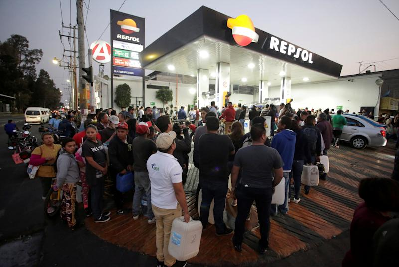 People stand in line at a gas station, in Mexico City
