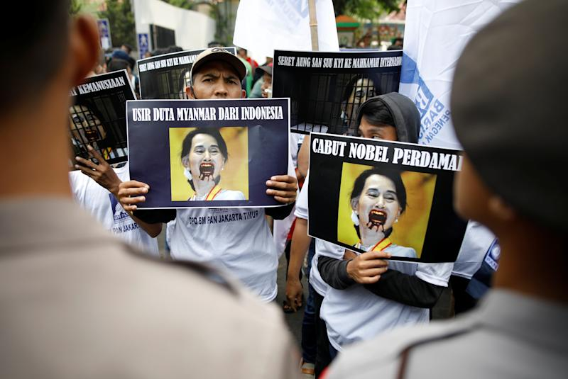 Protesters outside of Myanmar's embassy in Jakarta hold signs protesting Myanmar's government and Aung San Suu Kyi on Sept. 4, 2017. (Darren Whiteside/Reuters)