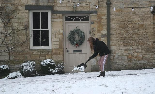 A woman clears snow from pathways