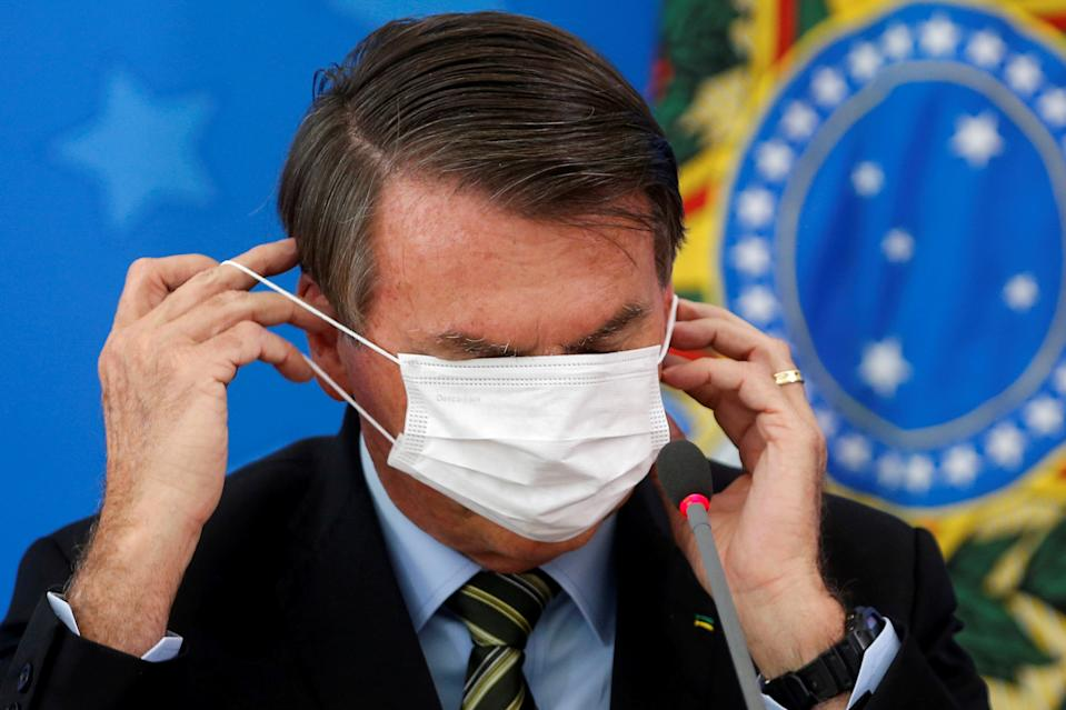 Brazil's Jair Bolsonaro adjusts his protective face mask during a news conference to announce measures to curb the spread of the coronavirus disease (COVID-19) in Brasilia, Brazil March 18, 2020. REUTERS/Adriano Machado     TPX IMAGES OF THE DAY