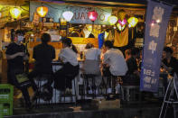 People gather at a bar after government imposed 8 p.m. closing time for restaurants and bars under Tokyo's fourth state of emergency Saturday, July 17, 2021, in Tokyo. The latest state of emergency has asked restaurants and bars to close by 8 p.m., if not entirely. This has pushed people to drink outside, although many bars remain open and bustling with customers who are defying the rules and expressing frustration and indifference. (AP Photo/Kiichiro Sato)