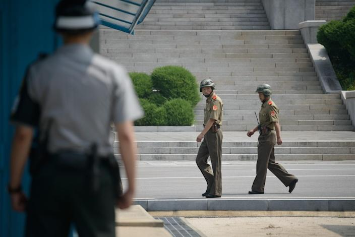 North Korean soldiers (C) walk past a South Korean soldier at Panmunjom near the demarcation line of the demilitarised zone dividing the peninsula (AFP Photo/Ed Jones)