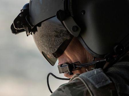 FILE PHOTO: A partial view of the Iraqi capital Baghdad is reflected in the visor of a U.S. Army helicopter crew member as he looks out of a Chinook helicopter flying from the U.S. Embassy to Baghdad International airport on January 9, 2019.  Andrew Caballero-Reynolds/File Photo
