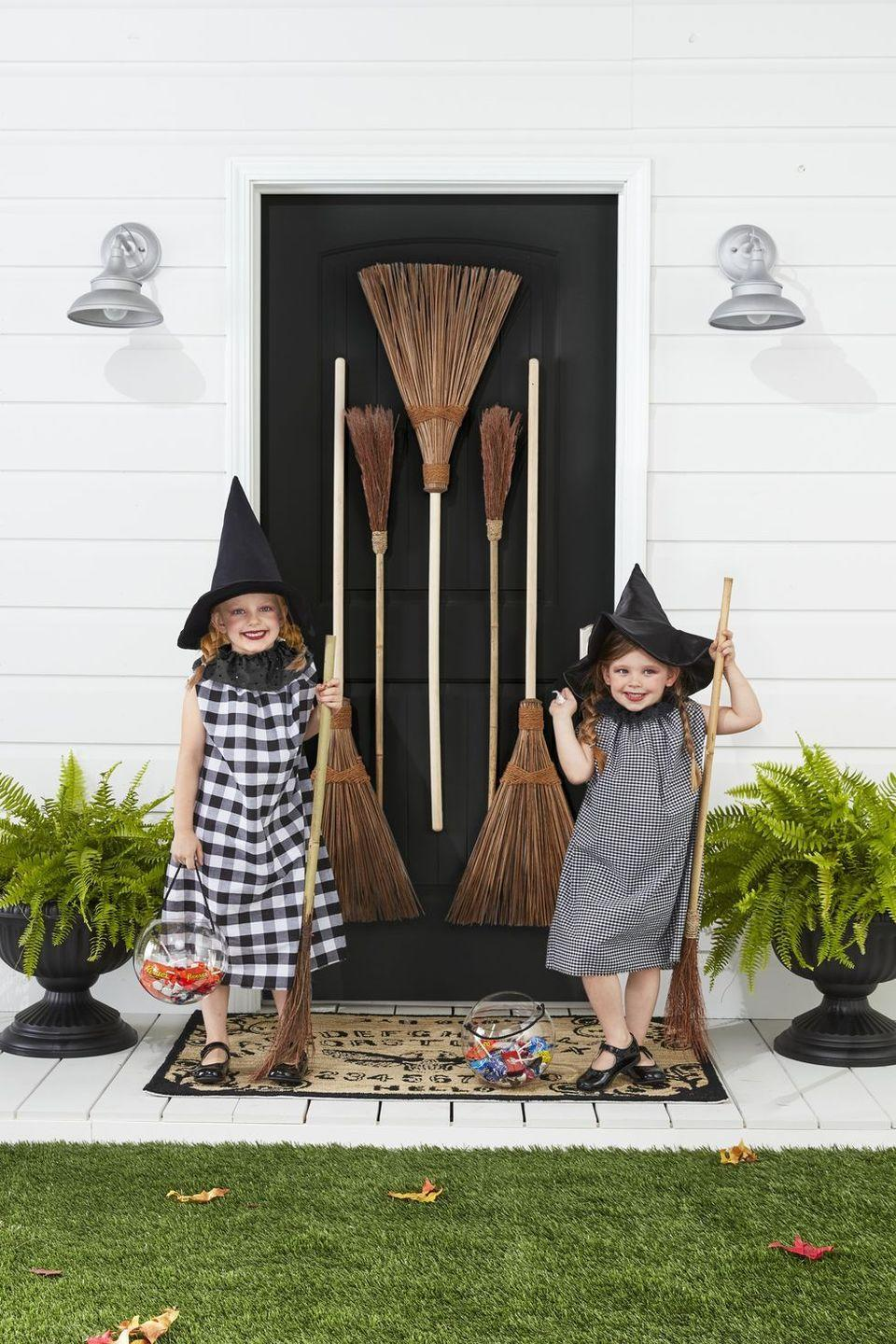 """<p>These country-chic witches have us giggling. Get your kids ready to cast some spells in no time with this last-minute <a href=""""https://www.countryliving.com/diy-crafts/g28304812/diy-witch-costume/"""" rel=""""nofollow noopener"""" target=""""_blank"""" data-ylk=""""slk:witch costume"""" class=""""link rapid-noclick-resp"""">witch costume</a> idea!</p><p><strong>Make the Costumes: </strong>Cut two 31- by 20-inch rectangles from black-and-white gingham fabric. Sew ends together, leaving armholes toward the top of the rectangle. Fold in the top 1 inch of the fabric and sew a channel, leaving a 1-inch opening. Thread a ribbon or string through the channel. Once on, pull the ribbon to gather it at the top. Cut a 3 1/2- by 36-inch strip from black eyelet fabric. Sew a hand-running stitch along the edge of one of the long sides. Leave a knot at one end and pull the string on the other side to create gathers. Pin at the back of the costume or add a snap. Finish with witches hats.</p><p><a class=""""link rapid-noclick-resp"""" href=""""https://www.amazon.com/Vesil-Black-Halloween-Costumes-Accessory/dp/B08GCGKSHZ/ref=sr_1_9?tag=syn-yahoo-20&ascsubtag=%5Bartid%7C10050.g.23785711%5Bsrc%7Cyahoo-us"""" rel=""""nofollow noopener"""" target=""""_blank"""" data-ylk=""""slk:SHOP WITCHES HATS"""">SHOP WITCHES HATS</a></p>"""