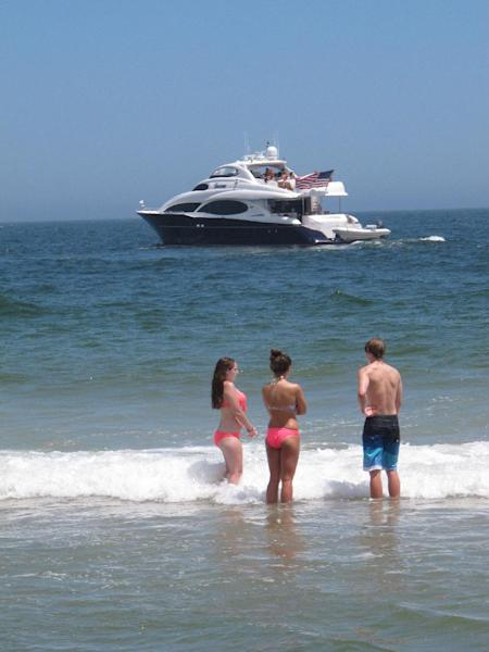 In this July 5, 2013 photo, swimmers in Point Pleasant Beach N.J. watch a large yacht turn around near the beach. A new Monmouth University/Asbury Park Press poll finds nearly 40 percent of New Jerseyans spent less time at the shore this summer, many fearing that businesses had not reopened after Superstorm Sandy last October. (AP Photo/Wayne Parry)