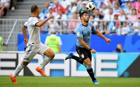 Luis Suarez battles for possession with Sergey Ignashevich of Russia during the 2018 FIFA World Cup Russia group A match between Uruguay and Russia at Samara Arena on June 25, 2018 in Samara, Russia - Credit: Getty Images