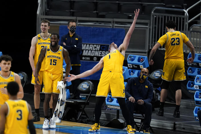 Michigan center Hunter Dickinson (1) celebrates with teammates at the end of a Sweet 16 game against Florida State in the NCAA men's college basketball tournament at Bankers Life Fieldhouse, Sunday, March 28, 2021, in Indianapolis. Michigan won 76-58. (AP Photo/Jeff Roberson)