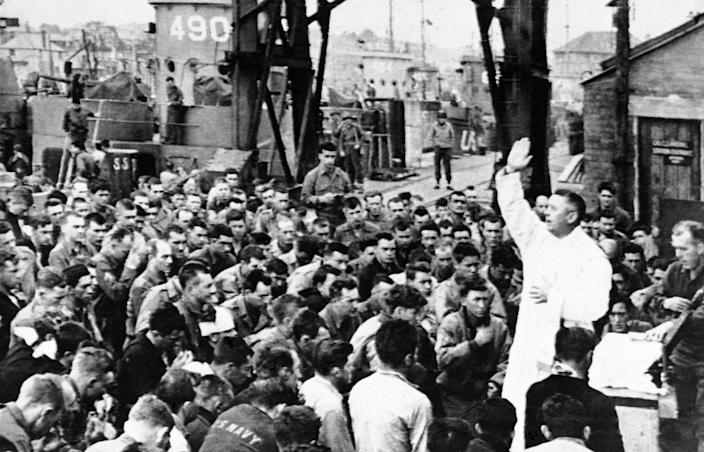 These members of the first groups of assault troops to take part in the Allied invasion of Northern France receive a benediction from an Army chaplain before leaving England on June 6, 1944, for the European continent. Their assault craft can be seen in the background. (Photo: AP)