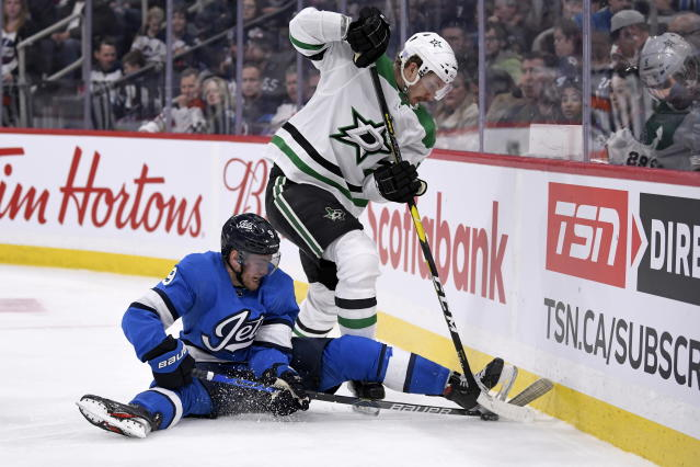 Winnipeg Jets' Andrew Copp (9) and Dallas Stars' Jamie Oleksiak (2) battle for the puck during second-period NHL hockey game action in Winnipeg, Manitoba, Sunday, Nov. 10, 2019. (Fred Greenslade/The Canadian Press via AP)