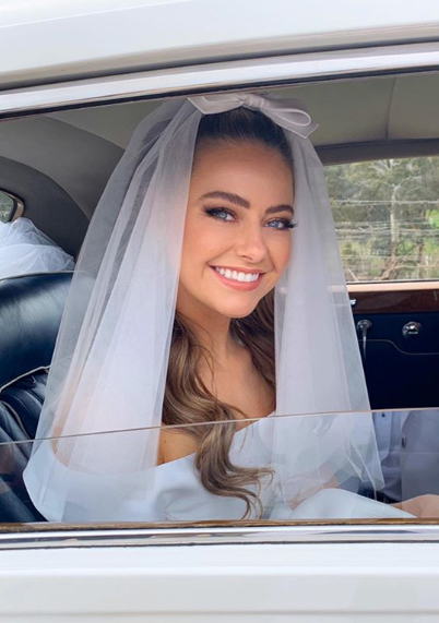 A photo of April Rose Pengilly wearing a white wedding dress on set of her TV wedding on Neighbours.