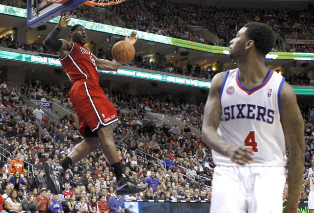 Miami Heat forward LeBron James dunks the ball near the Philadelphia 76ers forward Dorell Wright (4) during their NBA basketball game in Philadelphia, Pennsylvania, February 23, 2013. REUTERS/Tim Shaffer(UNITED STATES - Tags: SPORT BASKETBALL TPX IMAGES OF THE DAY) - RTR3E70B
