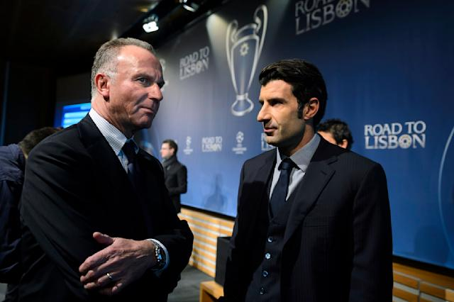 Bayern Munich CEO Karl-Heinz Rummenigge, left, speaks with Former Portugal's soccer player and Champions League Lisbon final ambassador Luis Figo, right, after the draw of the round of 16 games of UEFA Champions League 2013/14 at the UEFA Headquarters in Nyon, Switzerland, Monday, Dec. 16, 2013. (AP Photo/Keystone,Laurent Gillieron)
