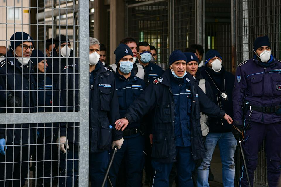 Prison police officers stand guard at the entrance of the Sant'Anna prison in Modena, Emilia-Romagna, in one of Italy's quarantine red zones on March 9, 2020. - Inmates in four Italian prisons have revolted over new rules introduced to contain the coronavirus outbreak, leaving one prisoner dead and others injured, a prison rights group said on March 8. Prisoners at jails in Naples Poggioreale in the south, Modena in the north, Frosinone in central Italy and at Alexandria in the northwest had all revolted over measures including a ban on family visits, unions said. (Photo by Piero CRUCIATTI / AFP) (Photo by PIERO CRUCIATTI/AFP via Getty Images)