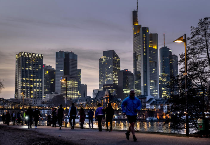 People stroll along the river Main with the buildings of the banking district in background in Frankfurt, Germany, Thursday, Feb. 25, 2021. (AP Photo/Michael Probst)