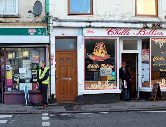 A teacher (left) standing guard outside Chilli Bellies in Bristol. (SWNS)