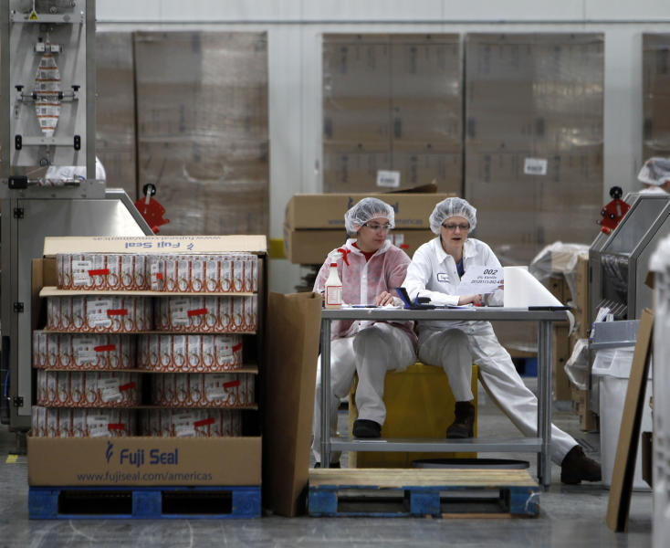 FILE -- In this Jan. 13, 2012 file photo, two women work in the sleeving plant where labels are put on containers at Chobani Greek Yogurt in South Edmeston, N.Y. Team USA sponsor Chobani, which is based in upstate New York, says it has 5,000 cups of Greek yogurt sitting in a refrigerated warehouse waiting to be flown to the Olympic village. But Russian authorities say the U.S. Department of Agriculture has refused to provide a certificate that is required for dairy products under its customs rules. A U.S. Department of Agriculture spokeswoman says the agency is working with its Russian counterpart to reach a solution to allow the Chobani shipment to go through despite the lack of agreement on general trade requirements for dairy products.(AP Photo/Mike Groll, File)