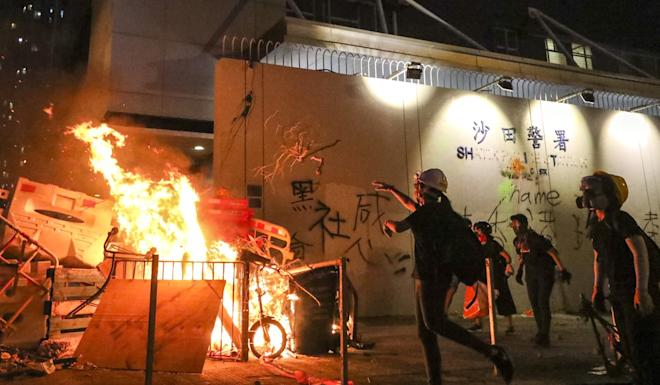 Protesters start a fire outside Sha Tin Police Station. Photo: Felix Wong