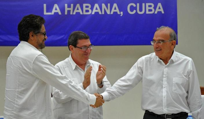 Colombian government delegation head Humberto de la Calle (R) and FARC-EP Commander Ivan Marquez (L) shake hands after signing a peace agreement at the Convention Palace in Havana, Cuba on August 24, 2016 (AFP Photo/Yamil Lage)