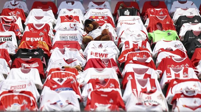 Shirts of fans unable to attend hang over the seats at the match between Cologne and Mainz (Lars Baron/AP)