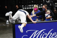 Dallas Mavericks guard Luka Doncic falls over a sign as he tried to save the ball from going out of bounds during the first half of the team's NBA basketball game against the Memphis Grizzlies on Tuesday, May 11, 2021, in Memphis, Tenn. (AP Photo/Wade Payne)