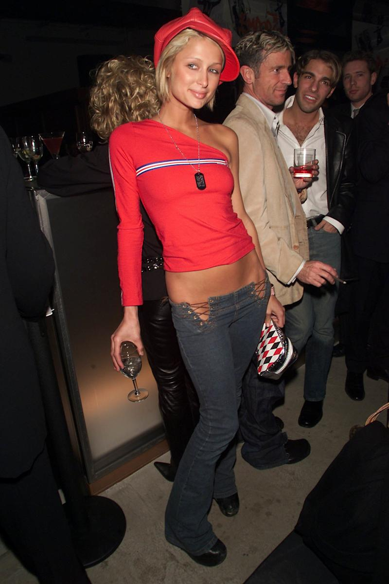 Paris Hilton attends an Armani Jeans and Vibe party wearing extremely low-waist, lace-up pants, a red one-shoulder top, and a matching beret.