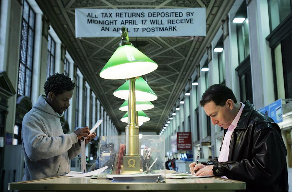 Kareem Lake (L) and Steve Harrison prepare their tax forms for mailing. (Photo: Mario Tama/Getty Images)