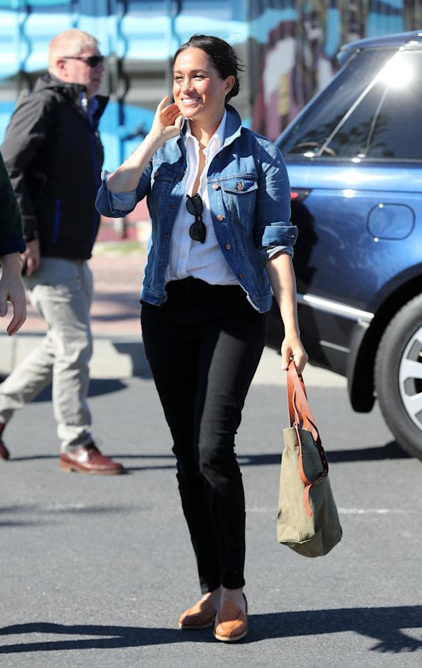"""The first outfit for day two of the tour brought out the Duchess of Sussex's casual side. She wore the white J.Crew blouse with <a href=""""https://brothervellies.com/products/blush-huaraches"""" rel=""""nofollow"""">tan flats from Brother Vellies</a>, black Mother jeans, and a <a href=""""https://click.linksynergy.com/deeplink?id=3r4YdkDiq/o&mid=1237&murl=https://shop.nordstrom.com/s/madewell-denim-jacket-regular-plus-size/4227861?origin=keywordsearch-personalizedsort&breadcrumb=Home%252FAll%2520Results&color=pinter%2520wash"""" rel=""""nofollow"""">denim jacket</a> and canvas tote from Madewell."""