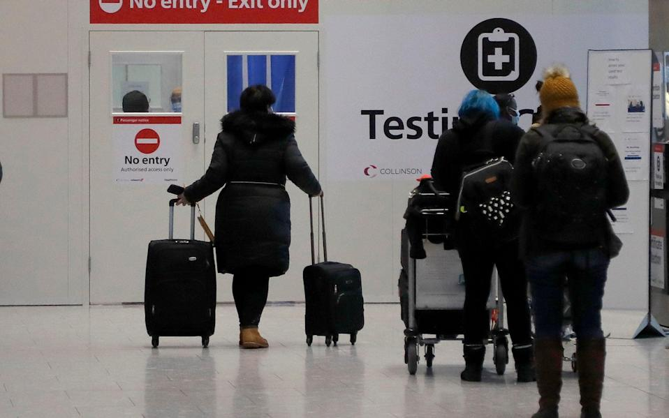 Travellers wait at the Covid-19 testing facility at Heathrow Airport in London - Frank Augstein/AP