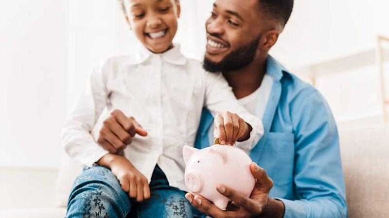 Girl and father putting coin into piggy bank, sitting on sofa at home