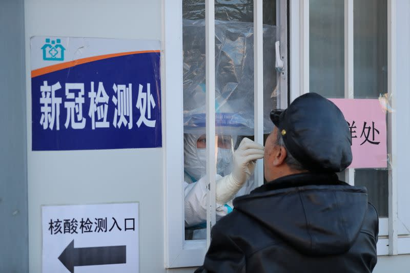 Medical worker collects a swab from a man for nucleic acid testing at a hospital in Shenyang