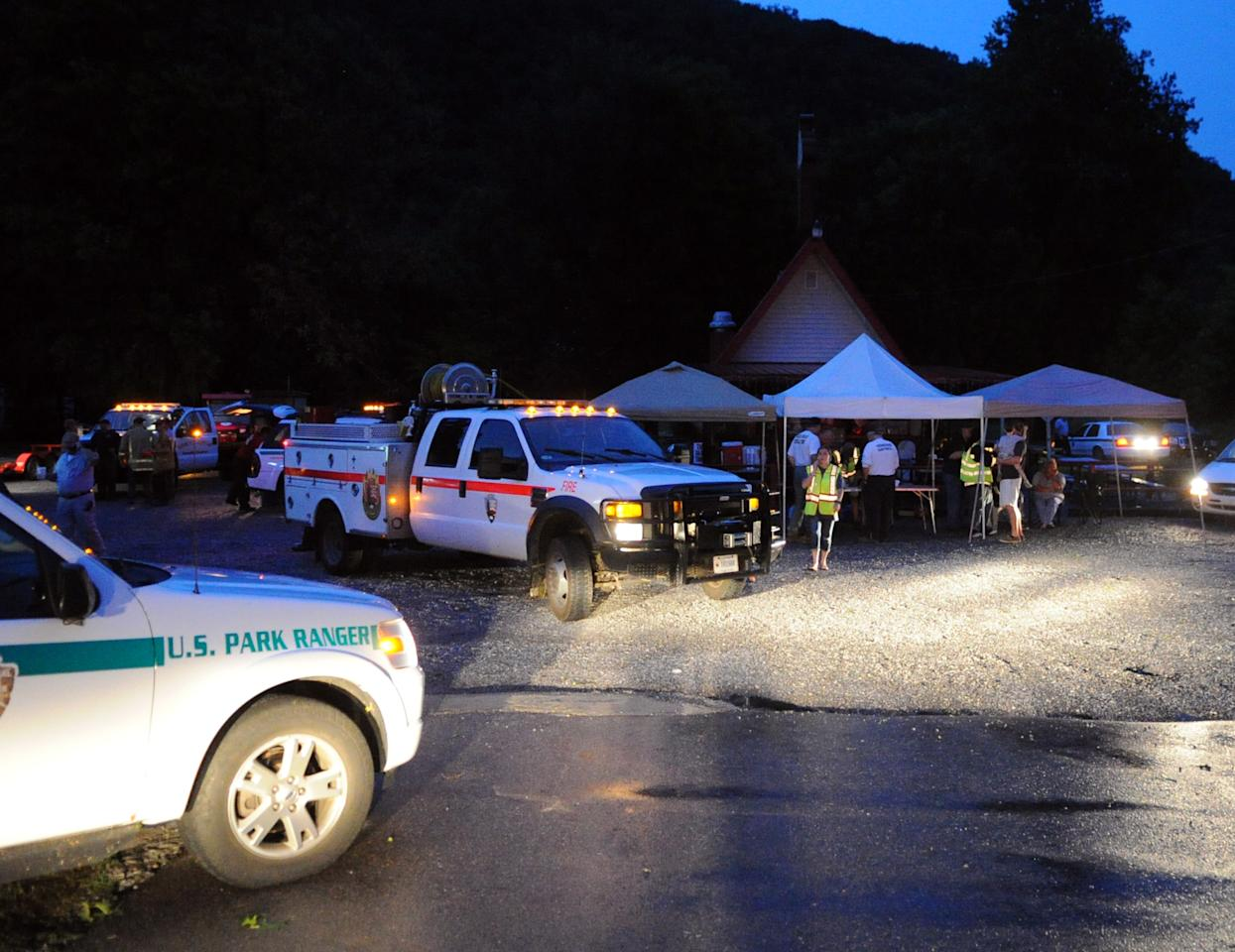 Rescue workers gather at a makeshift command at the Burger Master Drive-In in Townsend, Tenn., as crews arrive to help visitors to the Great Smoky Mountains National Park that are trapped in the Cades Cove area after a storm caused severe damage Thursday, July 5, 2012. According to the park's Deputy Superintendent Kevin Fitzgerald, hundreds of trees were downed during the storm and crews are working to clear them in order to gain access to those who are trapped. (AP Photo/Knoxville News Sentinel, Adam Brimer)