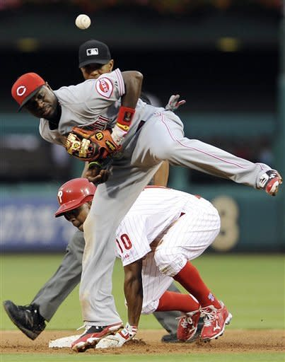 Philadelphia Phillies' Juan Pierre slides safely to second base past Cincinnati Reds' Brandon Phillips who can't pull in a wild throw in the first inning of a baseball game on Monday, Aug. 20, 2012, in Philadelphia. (AP Photo/Michael Perez)