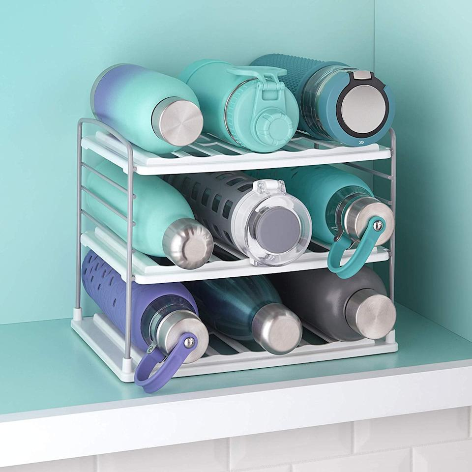 """<p>Reusable water bottles can take up a lot of space and end up rolling around, so keep them together with this <a href=""""https://www.popsugar.com/buy/YouCopia-UpSpace-Water-Bottle-Organizer-538987?p_name=YouCopia%20UpSpace%20Water%20Bottle%20Organizer&retailer=amazon.com&pid=538987&price=25&evar1=casa%3Aus&evar9=47132251&evar98=https%3A%2F%2Fwww.popsugar.com%2Fhome%2Fphoto-gallery%2F47132251%2Fimage%2F47132274%2FYouCopia-UpSpace-Water-Bottle-Organizer&list1=shopping%2Corganization%2Ckitchens%2Csmall%20space%20living%2Chome%20organization%2Chome%20shopping&prop13=mobile&pdata=1"""" rel=""""nofollow"""" data-shoppable-link=""""1"""" target=""""_blank"""" class=""""ga-track"""" data-ga-category=""""Related"""" data-ga-label=""""https://www.amazon.com/YouCopia-50185-UpSpace-Bottle-Organizer/dp/B081F99RWP/ref=sr_1_22?keywords=youcopia&amp;qid=1578684268&amp;smid=ATVPDKIKX0DER&amp;sr=8-22&amp;th=1"""" data-ga-action=""""In-Line Links"""">YouCopia UpSpace Water Bottle Organizer</a> ($25).</p>"""